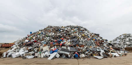 returned: Dumping ground. Scrap metal heap. Compressed crushed cars is returned for recycling. Iron waste ground in the industrial area. Stacked automobile