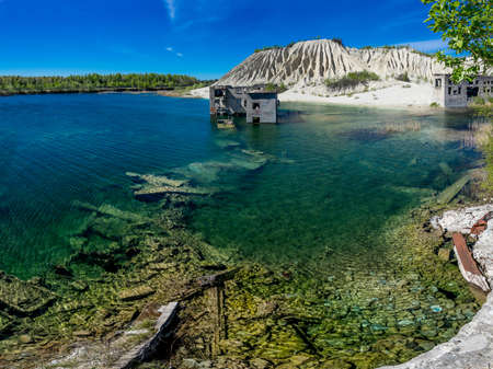 Abandoned mines and hauses. Quarry and old prison architecture. Crystal clear blue water, lake and mountain. The ashes dunes in  Estonia, Europe.