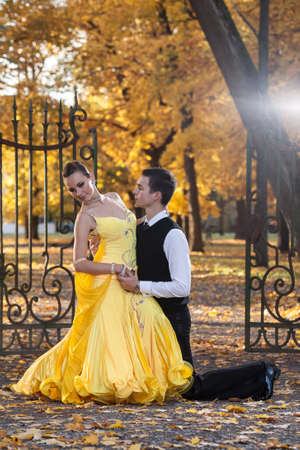 Pair of dancers dancing in the  palace garden. Man with suit and woman in a yellow long dress  in the middle of the park in autumn. Dry fallen colored leaves, trees gates in background