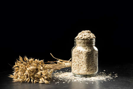 Oat bunch and flakes in flavouring jar, isolated on black background. Grain bouquet, golden oats spikelets on dark wooden table, can filled with dried grains. Food, bakery concept
