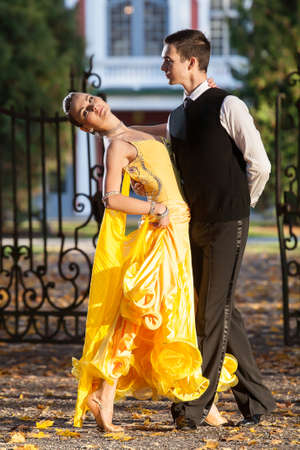dry suit: Pair of dancers dancing in the  palace garden. Man with suit and woman in a yellow long dress  in the middle of the park in autumn. Dry fallen colored leaves, trees gates and castle in background Stock Photo