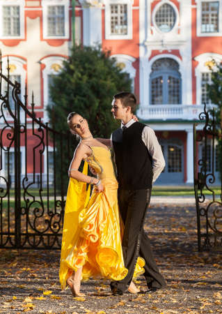 wicket door: Pair of dancers dancing in the  palace garden. Man with suit and woman in a yellow long dress  in the middle of the park in autumn. Dry fallen colored leaves, trees gates and castle in background Stock Photo