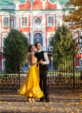 Pair of dancers dancing in the  palace garden. Man with suit and woman in a yellow long dress  in the middle of the park in autumn. Dry fallen colored leaves, trees gates and castle in background Stock Photo
