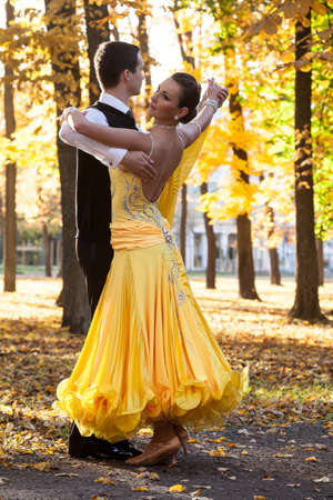 dry suit: Pair of dancers dancing in the woods. Man with suit, woman in yellow long dress  middle of the palace park in autumn. Dry fallen colored leaves, deciduous trees, natural environment. Nature background Stock Photo