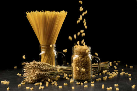 Wheat bunch, macaroni and pasta in jar, isolated on black background. Grain bouquet, golden spikelets on dark wooden table. Food, bakery concept Stock Photo
