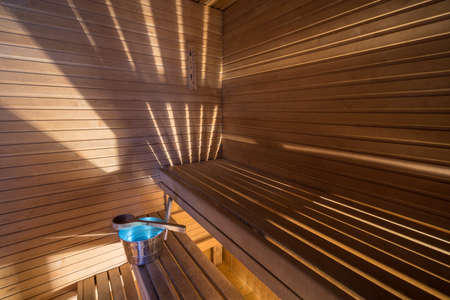 Wellness and spa conception. Sauna bath bucket with blue water, scoop, striped light, wooden walls and timber bench Stock Photo