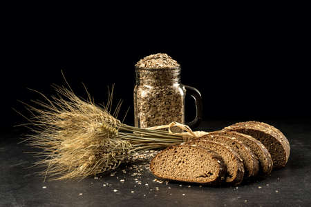 Grain bouquet, golden oats spikelets in jar on dark wooden table, buns and can filled with dried grains. Food, bakery concept Stock Photo