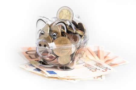Spaarvarken, munten en euro rekeningen. Geldbesparend concept. Bankbiljettenclose-up, geïsoleerde achtergrond. Stockfoto