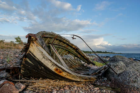 Old boat, shore, evening light, sunset, clouds and architecture concept in the Baltic Sea. Mohni, small island in Estonia, Europe.