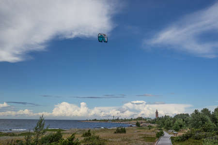 A kite surfer rides on the sea. Kites in the sky. Kite Boarding, extreme sport on Mohni, small island in Estonia, Europe.