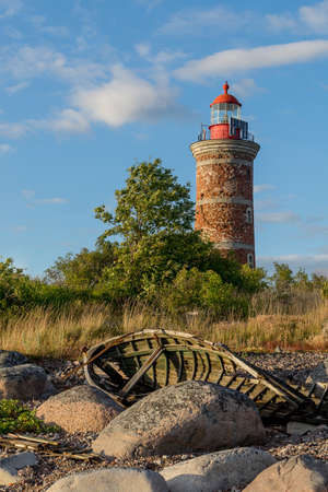 Lighthouse and old boat in the Baltic Sea. Shore, evening light, sunset, clouds and architecture concept. Mohni, small island in Estonia, Europe.