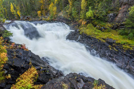 Cliff, stone wall, forest, waterfall and wild river view in autumn. Fall colors - ruska time in Myllykoski. One part of Karhunkierros Trail. Oulanka National Park in north Finland. Lapland, Europe Stock Photo