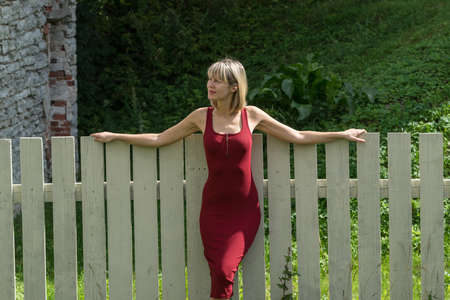 Young blond woman in a red dress leaning against the wooden fence. Stock Photo