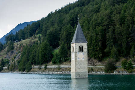 Church under water, drowned village, mountains landscape and peaks in background. Reschensee Lake Reschen Lago di Resia. Italy, Europe, Südtirol, South Tyrol, Upper Adige, Alto Adige