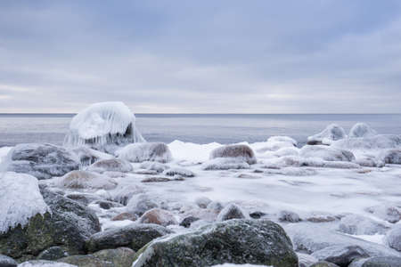 Rocky beach on wintertime. Evening light and icy weather on shore like fairy tale country. Winter on coast. Blue sky, white snow, ice covers the land on seaside. Waterside on Juminda, Estonia, Europe 스톡 콘텐츠