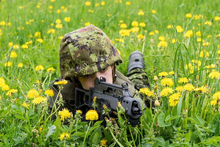 Portrait of armed woman with camouflage. Young female soldier observe with firearm. Child soldier with gun in war, green goutweed and yellow dandelions background.  Military, army people concept