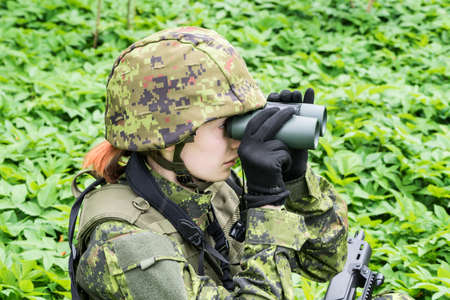 Portrait of armed woman with camouflage. Young female soldier observe with binoculars. Child soldier with gun in war, green goutweed background.  Military, army people concept