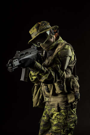 Portrait of armed woman with camouflage. Young female airsoft sniper observe with firearm. Soldier with gun in war, black background.  Military, army people concept Stock Photo