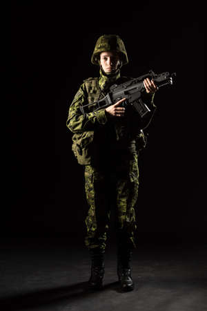 Portrait of armed woman with camouflage. Young female soldier observe with firearm. Child soldier with gun in war, black background.  Military, army people concept