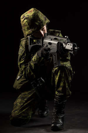 Portrait of armed woman with camouflage. Young female soldier observe with firearm. Child soldier with gun and binoculars in war, black background.  Military, army people concept