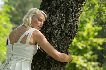 Blonde woman hugging a tree in park. Young girl resting in nature, leaned against a tree Stock Photo