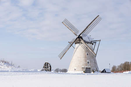 Grain mill on the winter landscape. Dutch windmill and natural background pattern Stock Photo