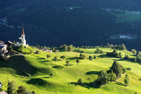 Chapel and sheep on the meadow. Bell tower, trees, shrubs and hilly green grassland. Heiliger Antoniuse church and houses in the evening light. Pitburger See, Taxegg, Salzburg, Austria, Europe