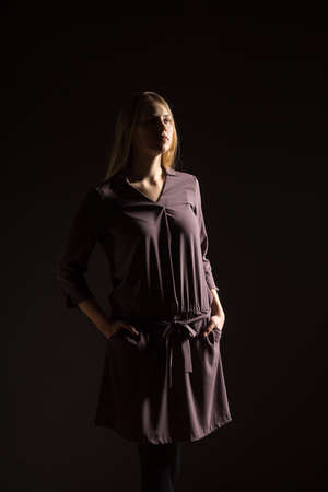 Caucasian white female model portrait. Beautiful girl, long blonde hair. Woman posing studio shot on a black background Фото со стока