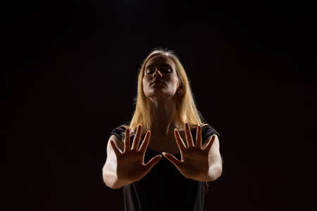 Young woman waving her hands. Blonde girl expressing with raised hands their emotions in a studio on a black background
