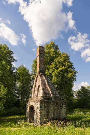 Abandoned ruin of oven chimney. Broken furnace. Green meadow environment and blue sky background Foto de archivo