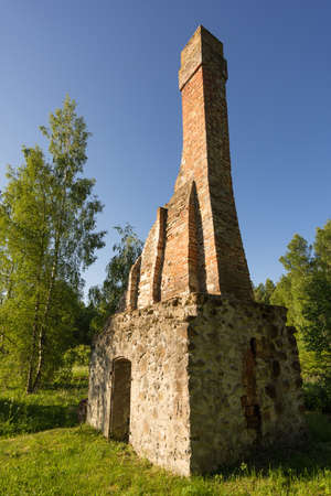 Abandoned ruin of oven chimney. Broken furnace. Green meadow environment and blue sky background