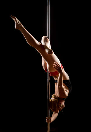 Woman performs pole dance on the stage. Girl whirls around the pole while performing dance or yoga  in the studio. Blonde lady dancing a striptease