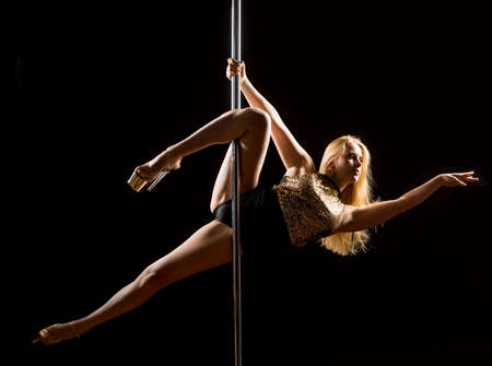 Woman performs pole dance on the stage. Girl whirls around the pole while performing dance or yoga  in the studio. Blonde lady dancing a striptease Фото со стока - 112610211