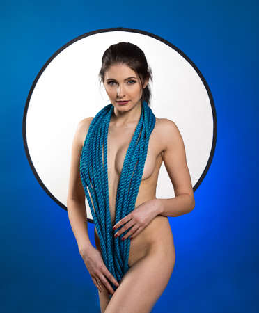 Young nude woman with make up. Model with rope. Naked girl beauty portrait on blue background.