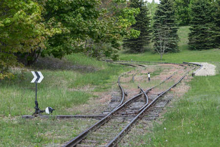 Railroad tracks stretches and green grass and trees. Railway road environment background.End of the rail.