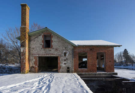 Ancient abandoned water mill surrounded by beautiful nature. House built of stone and wood. The land is white, snowy in the winter Archivio Fotografico