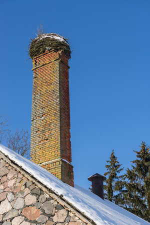 Abandoned ruin of oven chimney. Broken furnace. Snowy roof, stork slot and blue sky background in the winter Stock Photo