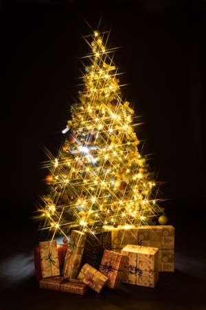 Cadeaux et bokeh d'arbre de Noël doré sur fond noir Banque d'images