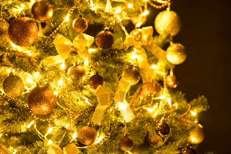 Golden Christmas tree with decorations and lights bokeh in a black background