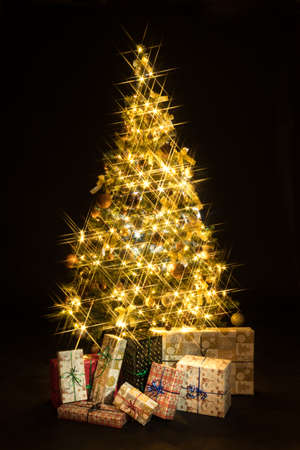 Gifts and golden Christmas tree bokeh in a black background Reklamní fotografie