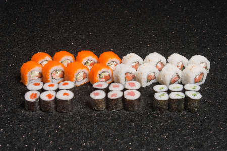 Sushi rolls on black marble background. Fresh Hosomak, Maki, Nigiri, Tempura, Uramaki, Philadelphia pieces with rice, nori and fish. Japanese cusine, Asian food. Stock Photo - 129929828