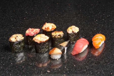 Sushi rolls on black marble background. Fresh Hosomak, Maki, Nigiri, Tempura, Uramaki, Philadelphia pieces with rice, nori and fish. Japanese cusine, Asian food.