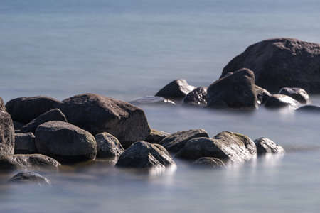 Calm blue see and big stones on the beachbeach,  免版税图像