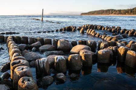 Embedded stones and harbor ruins in Narva-Jõesuu. Rocky beach, peaceful sea and port. Harbour Ida-Viru County, Narva, Estonia. Baltic sea, Europe