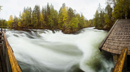 Cliff, stone wall, forest, waterfall and wild river panoramic view in autumn. Fall colors - ruska time in Myllykoski. Karhunkierros Trail, Oulanka National Park in north Finland. Lapland, Europe