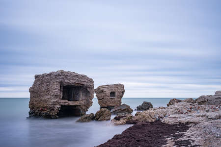 Liepaja beach bunker. Brick house, soft water, waves and rocks. Abandoned military ruins facilities in a stormy sea. Barracks building in the Baltic sea.  Liepaja, Latvia, Europe. Stock Photo