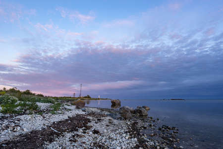 Skew lighthouse in the Baltic Sea. Shore, evening light, sunset, moon and architecture concept. Harilaid, small island in Estonia, Europe. Stock Photo