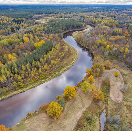 Forest in autumn colors. Colored trees and a meandering blue river. Red, yellow, orange, green deciduous trees in fall. Koiva national park, Latvia, Europe