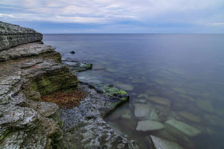 Stone wall on the Baltic sea in the summer. Osmussaar coast, island in Estonia, Europe.