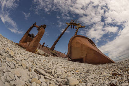 Old rusty wreck and rocky beach in Baltic Sea, natural environment. Osmussaar, Estonia, Europe.